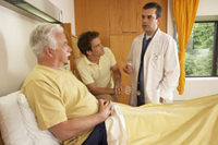 doctor conferring with older male patient as son listens