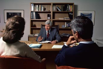 An attorney, in his office, talking to a couple