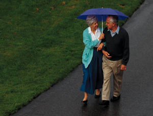 Older couple walking on a sidewalk under an umbrella