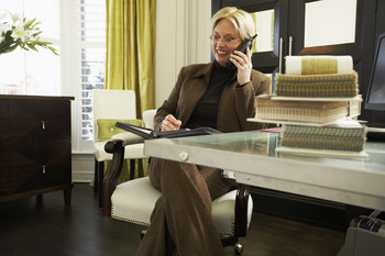 Image of a woman sitting at a desk talking on the phone